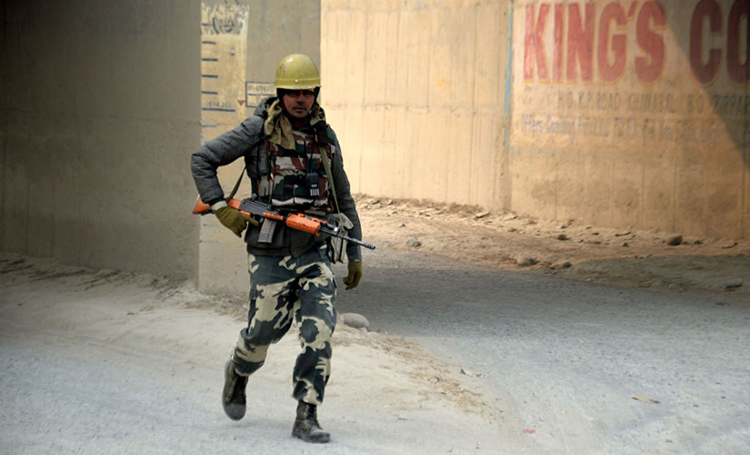 A member of the security force conducts a search during the encounter. Firstpost/Sameer Yasir