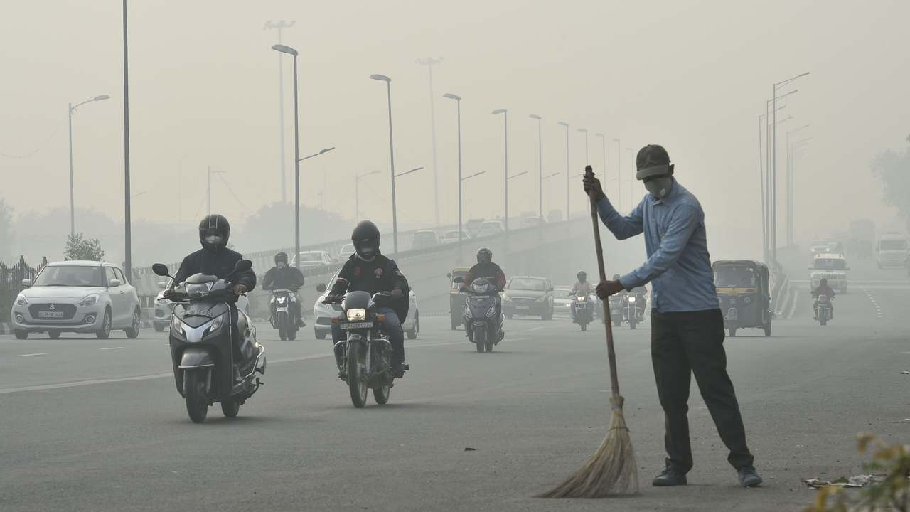 A civic worker, wearing an anti-pollution mask, sweeps the road amid heavy smog, in New Delhi, Friday, Nov. 15, 2019. A thick layer of toxic smog engulfed Delhi as the pollution level continued to remain in the 'severe' category for the fourth consecutive day in the capital. Image: PTI/Arun Sharma