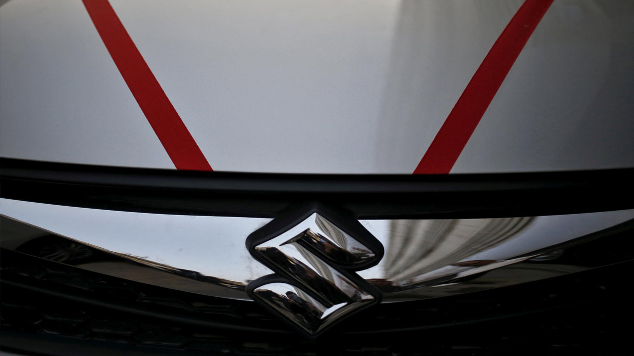 The logo of Maruti Suzuki India Limited is seen on car parked outside a showroom in New Delhi. Image: Reuters