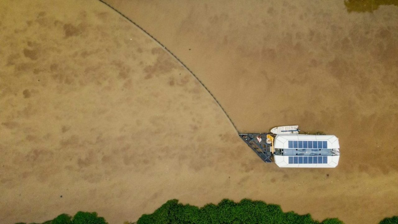 Aerial view of the prototype of the Interceptor, which was installed in Cengkareng drain in Jakarta, Indonesia, in May 2019. A long barrier guides trash toward the device's mouth. Image courtesy of The Ocean Cleanup.