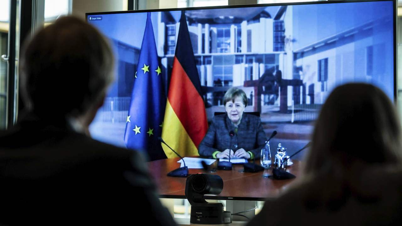 German Chancellor Angela Merkel displayed on a screen at the Environment Ministry as she delivers her speech at the Petersberg Climate Dialogue, in Berlin, Germany, Tuesday, April 28, 2020. Due to the coronavirus crisis, the conference will only be held digitally. (Michael Kappeler/Pool via AP)