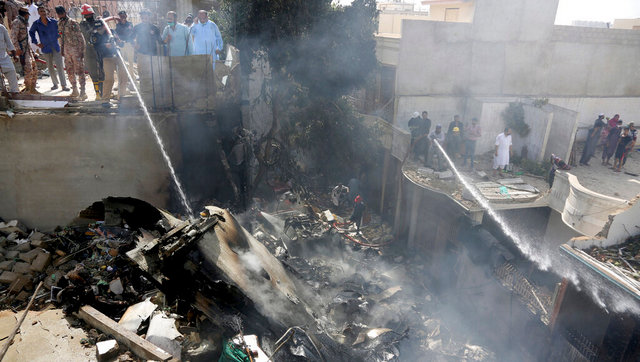 Fire brigade staff try to put out fire caused by plane crash in Karachi, Pakistan. AP