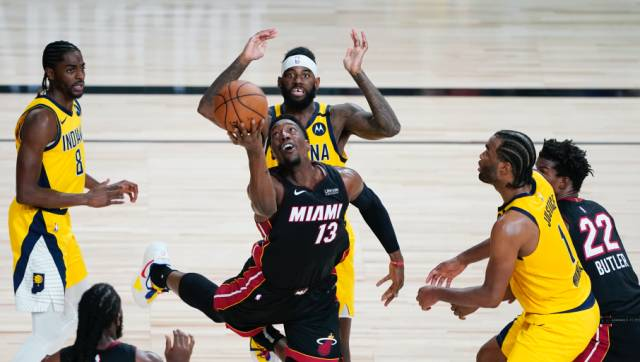 Miami Heat forward Bam Adebayo (13) makes a off-balanced shot between Indiana Pacers defenders Justin Holiday, left, JaKarr Sampson, center, and T.J. Warren (1) during the second half of an NBA basketball first round playoff game, Tuesday, Aug. 18, 2020, in Lake Buena Vista, Fla. (AP Photo/Ashley Landis, Pool)