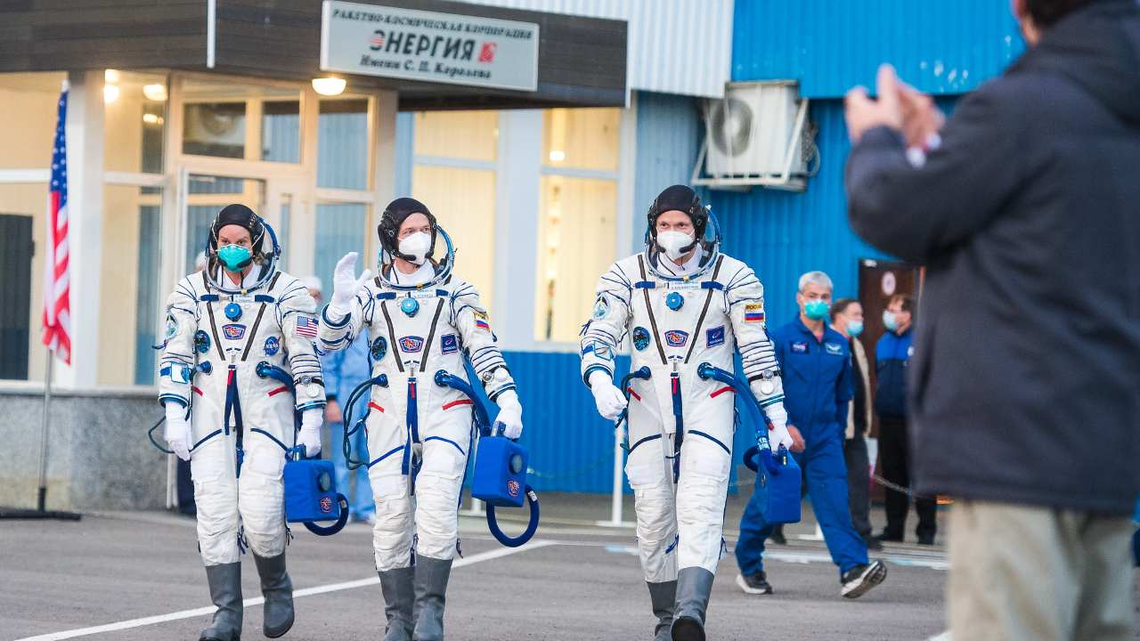 Expedition 64 NASA astronaut Kate Rubins, left, and Russian cosmonauts Sergey Ryzhikov, center, and Sergey Kud-Sverchkov, right, of Roscosmos are seen as they depart Building 254 to head to their launch onboard the Soyuz MS-17 spacecraft. Image credit: NASA/GCTC/Andrey Shelepin