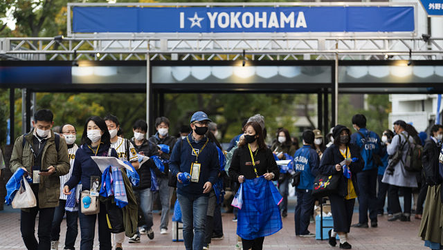 Fans enter a baseball stadium before a Japanese baseball league game between the Hanshin Tigers and the Yokohama DeNA BayStars in Yokohama on 30 October. AP Photo